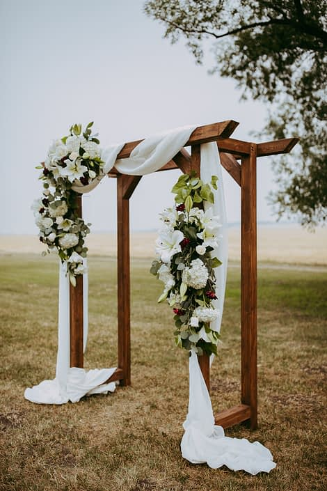 rustic wooden archway with white voile and stunning floral arrangements designed with white lilies and hydrangea and burgundy dahlia