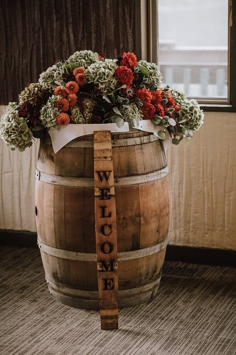 Rustic wedding welcome arrangement with welcome sign and flowers including green hydrangea and orange dahlia and red dahlia and red roses and blue eryngium