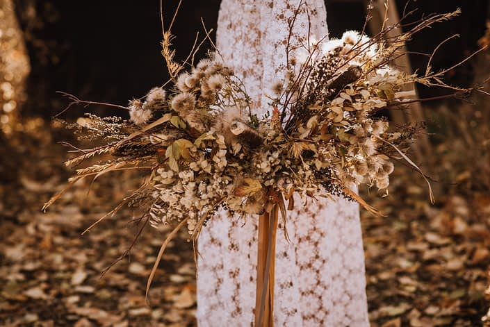 Fall boho bridal bouquet made with dried florals and trailing silk ribbons with lace dress