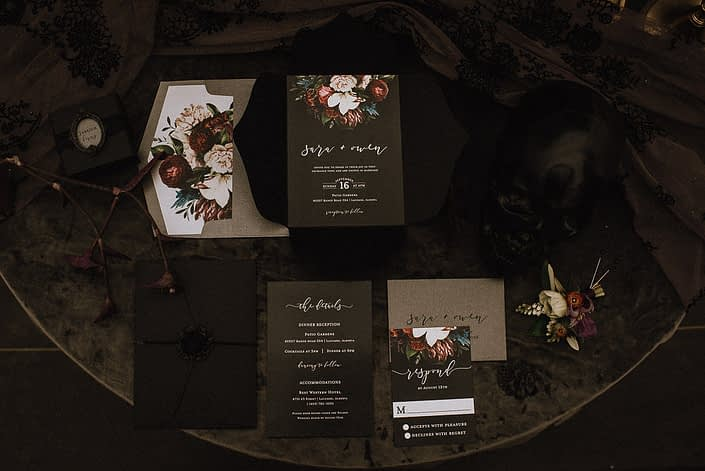 flat lay of black wedding invitations for alternative brides and grooms black skull and grey velvet and dark and moody