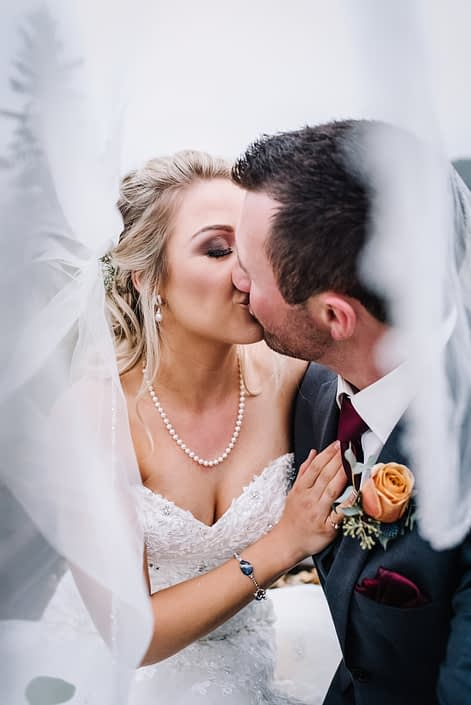 Groom kissing bride wearing a white veil with boutonierre designed with a peach rose and eucalyptus
