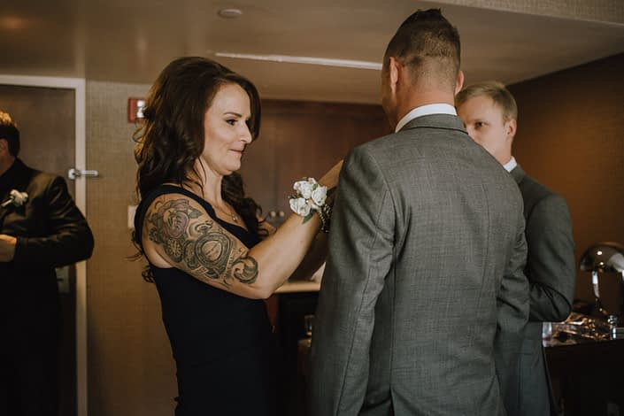 mother wearing white spray rose pearl wristlet corsage at hotel wedding