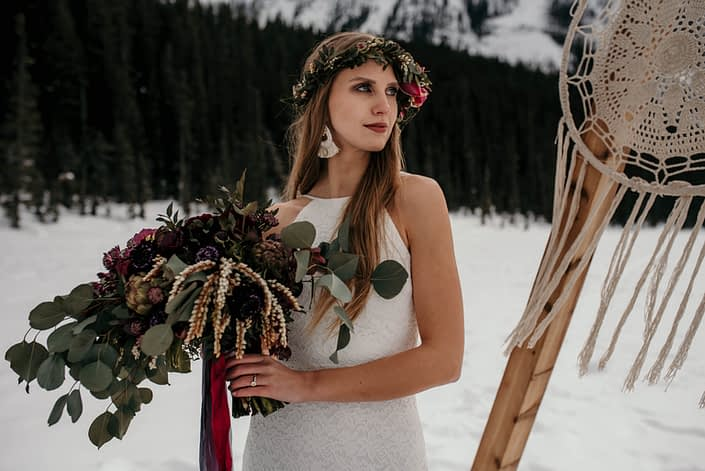 Boho bride in the winter with macrame backdrop and eucalyptus and burgundy bouquet wearing a greenery flowercrown