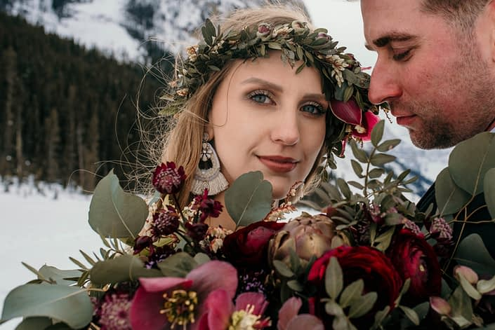 close up of bride with flower crown and burgundy ranunculus bridal bouquet