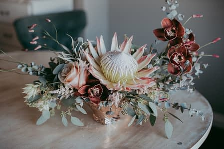 Tropical flower arrangement with copper cymbidium orchids, eucalyptus and blush king protea