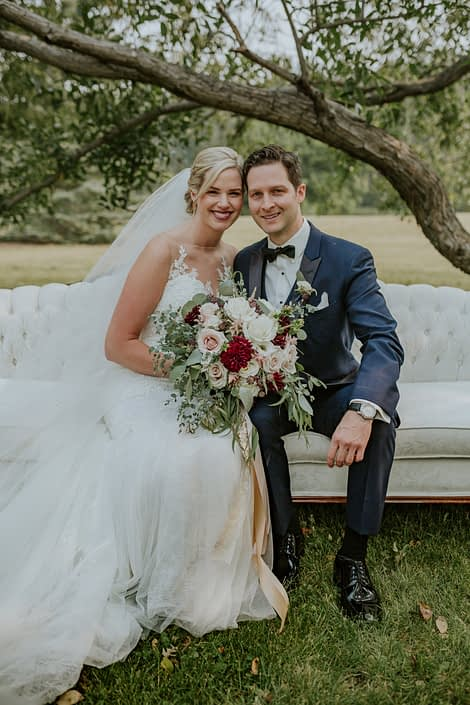 bride with veil and wedding dress and groom in navy tux sitting on an antique ivory sofa holding a blush, burgundy and ivory bridal bouquet with fresh eucalyptus greenery collar