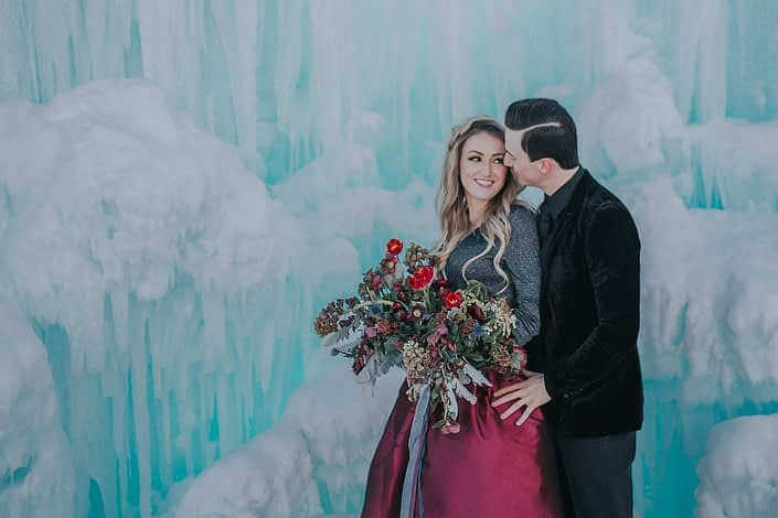 An organic bridal bouquet designed for an engagement shoot at the edmonton ice castles with red tulips, burgundy ranunculus and red heleborus