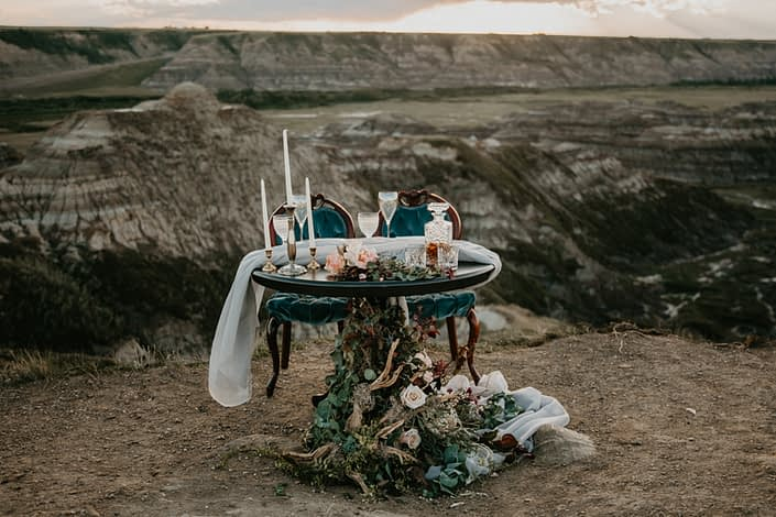 Photoshoot in the badlands with sweetheart table and floral arrangements designed in driftwood