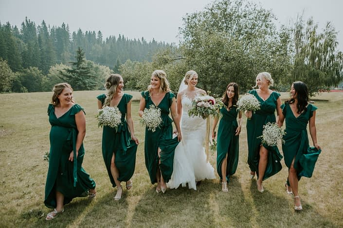 bride in white wedding dress with veil and bridesmaids in forest green holding bouquets designed with babies breath and eucalyptus
