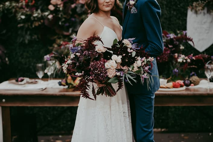 Close up of bridal bouquet designed with burgundy amarathus and hydrangea, blush spray roses and carnations and purple clematis and groom in navy blue suit in front of a boxwood backdrop