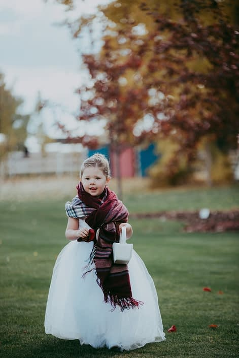 Fall wedding with flowergirl with plaid shawl walking down aisle with basket of red rose petals