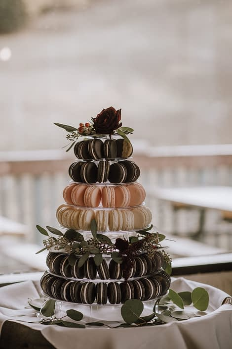 macaroon tower with floral accents including eucalyptus and red roses and hypericum berries