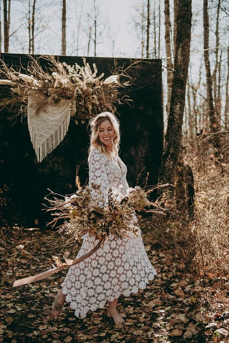 laughing blonde boho bride in crocheted dress in the fall in the woods on a sunny day with a foraged dried flower bouquet with fall colored trailing ribbons