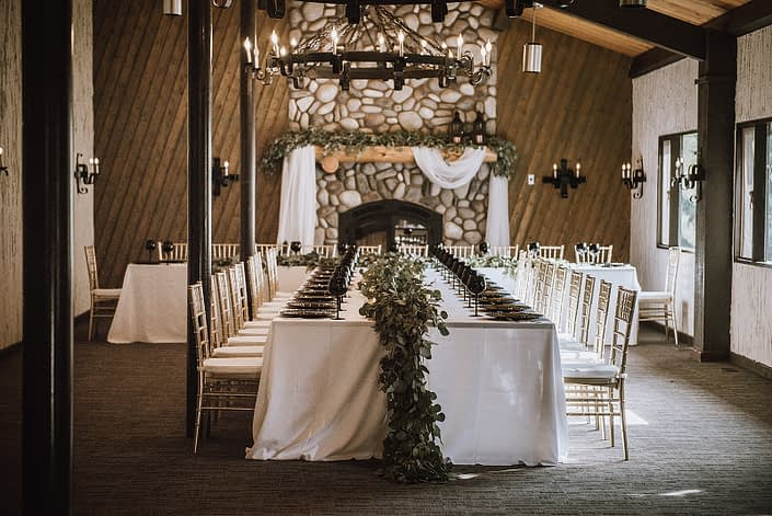 Wedding reception decor with white linens and black ine glasses and charger plates decorated with fresh eucalyptus garland and gold chiavari chairs