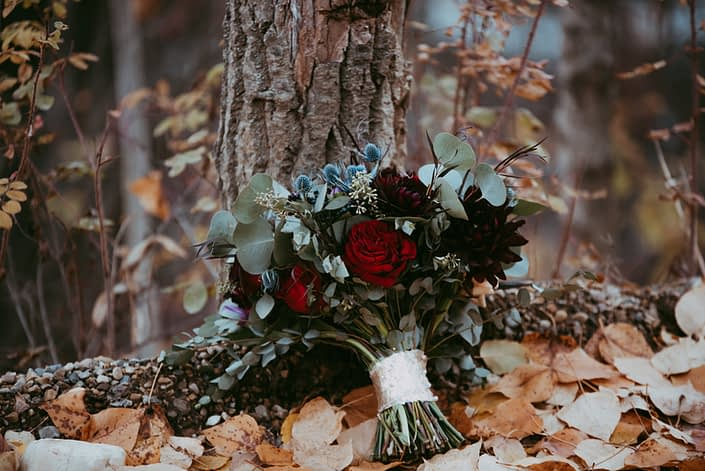 Handtied wedding bouquet in blue and burgandy with red garden roses burgundy dahlias eryngium mixed eucalyptus in rustic setting displayed in a forest in fall fall wedding at canyon ski resort in red deer, alberta