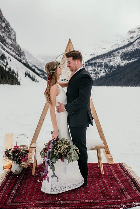lake louise elopment photoshoot with burgundy rug and triangle archway