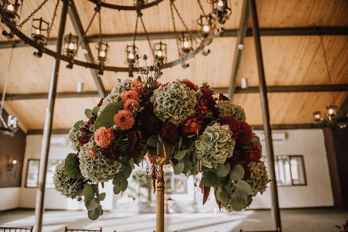 Breathtaking tall centerpiece atop a gold candelabra with green hydrangea and orange dahlias and red dahlias and eucalyptus and eryngium and red roses at Canyon Ski Resort in Red Deer Alberta