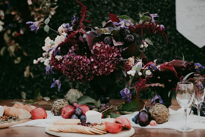 Boxwood wall backdrop with rustic harvest table with floral arrangement in a black compote with burgundy amaranthus and hydrangea, plum scabiosa, blush snowberries and purple carnations and fresh charcuterie boards