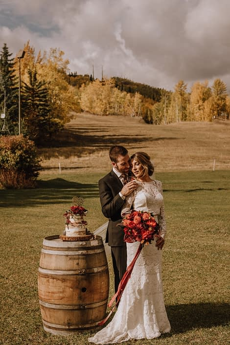 Bride and Groom at Canyon Skir Resort in the autumn holding a Dahlia bouquet in burgundy and burnt orange standing beside a rustic whiskey barrel with a naked wedding cake on it