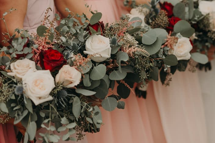 bouquet close up of blush wedding with red roses quicksand roses navy eryngium and pink astilbe and white o'hara garden roses and mixed eucalyptus
