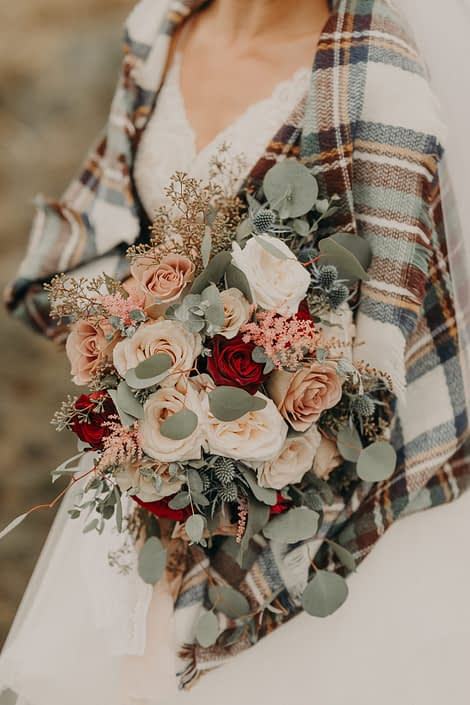 bride in plaid shawl with bouquet with red roses and quicksand roses and white o'hara garden roses and astilbe and eryngium and eucalyptus