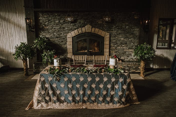 Sweetheart table at Canyon Ski Resort in Red Deer in front of fireplace with mixed greenery trees and greenery garland and his and hers naked cakes