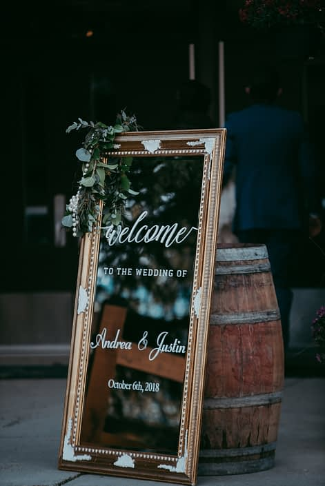 Mirrored sign with gold frame and mixed eucalyptus garland with floral accents and a rustic barrel