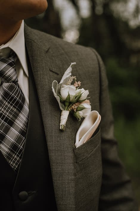 groom in charcoal grey suit with boutonniere of white spray roses and pale pink astilbe and dusty miller