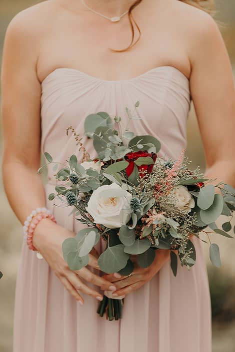 Blush bridesmaid dress with bouquet of white o'hara garden roses quicksand roses and red roses and eryngium and pink astilbe and mixed eucalyptus