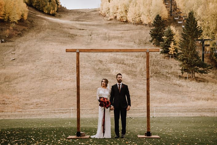 Bride and Grooms stand under a wooden archway at Canyon Ski Resort in the autumn Bride is holding a bouquet of dahlias in orange and burgundy