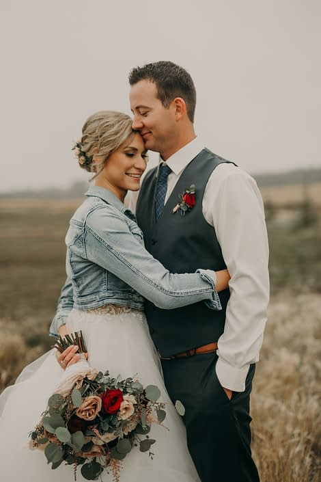 bride in jean jacket with groom in grey suit with red spray rose boutonniere and bouquet with blush and red roses and pink astilbe and eucalyptus in prairie field