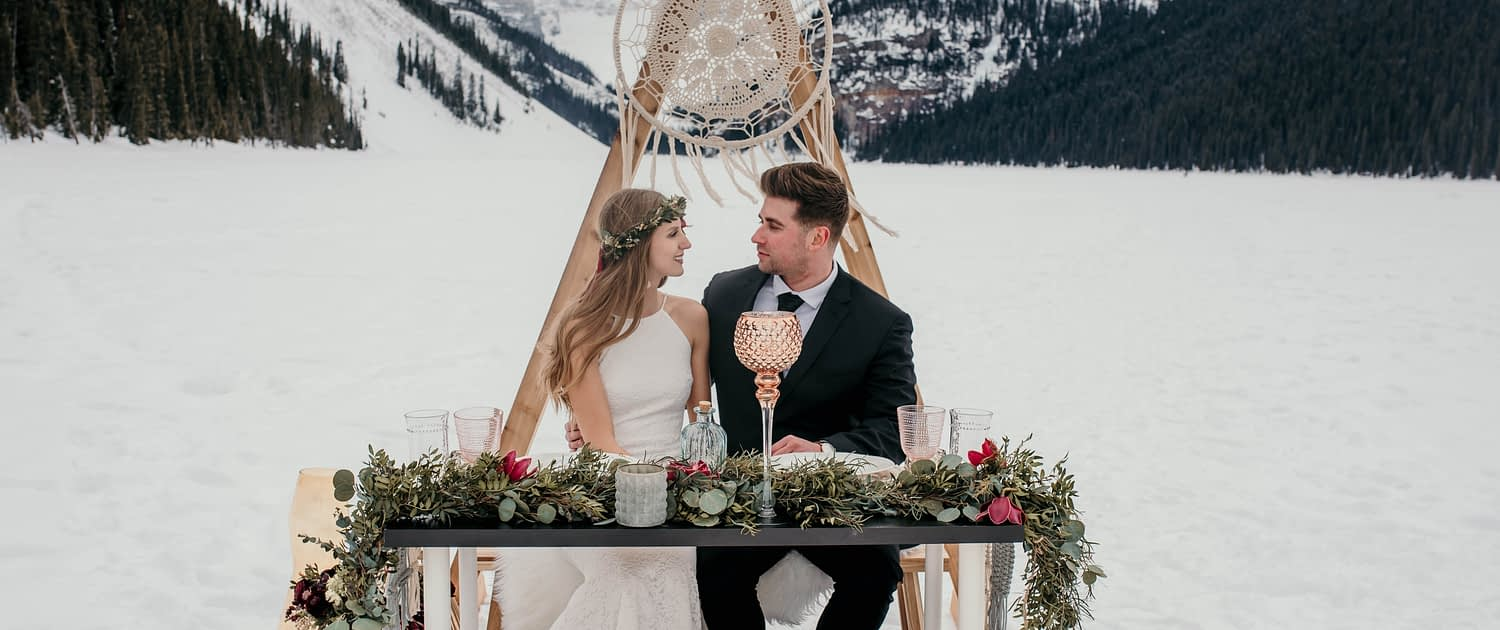 Boho style winter elopement at lake louise with macrame hoop and triangle archway