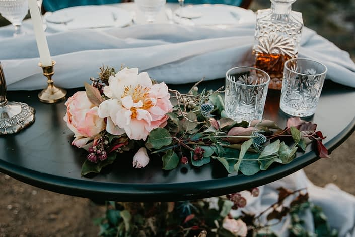 Sweetheart table with pale blush peonies and burgundy leaves