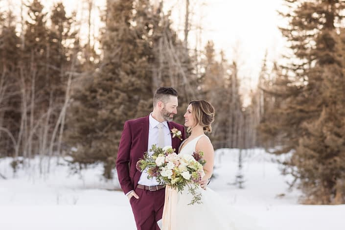 Winter bride and groom with wedding flowers of burgubdy hellebore, blush roses and ranunculus