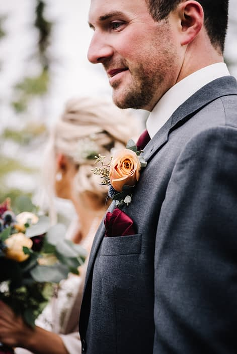Groom wearing a grey suit and boutonierre designed with a mustard yellow rose and eucalyptus