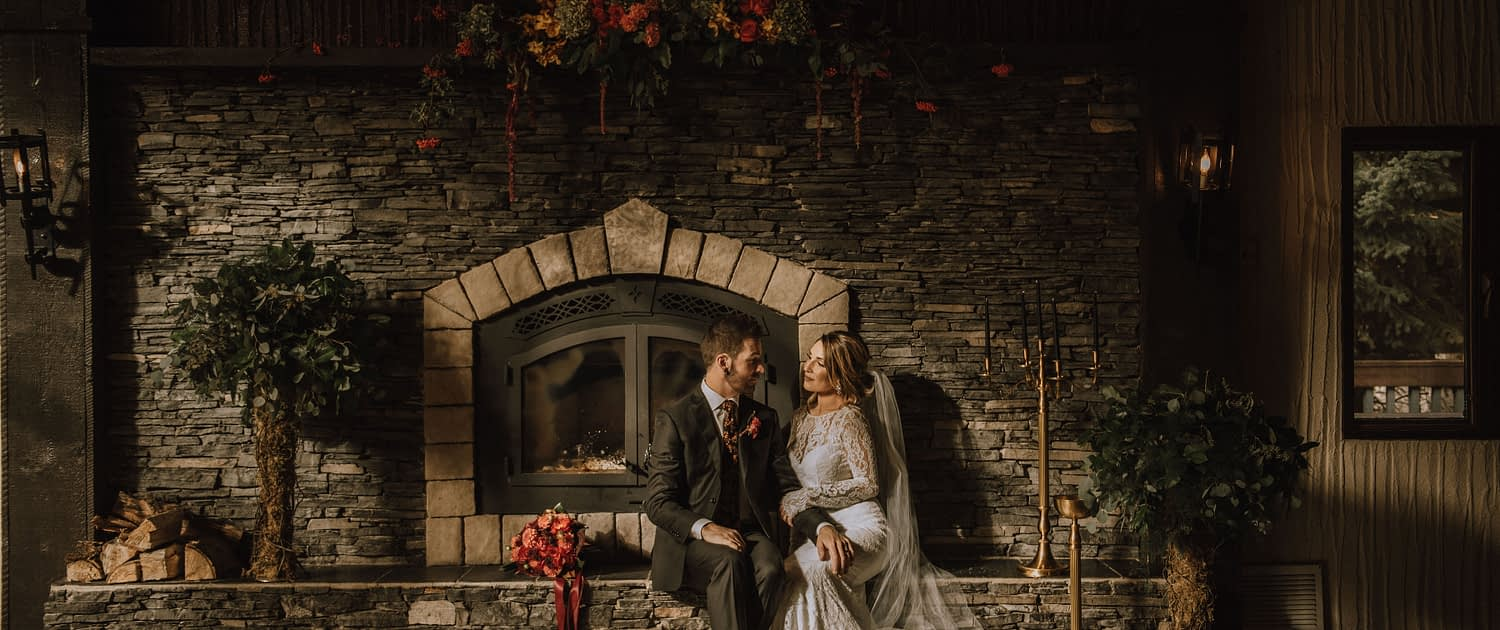 bride with lace dress and a long veil sit in front of a rustic FIreplace mantle backdrop with bride and groom and floral trees made with moss covered trunks and eucalyptus greenery toppers and a floral mantlepiece made with green hydrangea and orange dahlias and yellow mokaras and red amaranthus and red roses