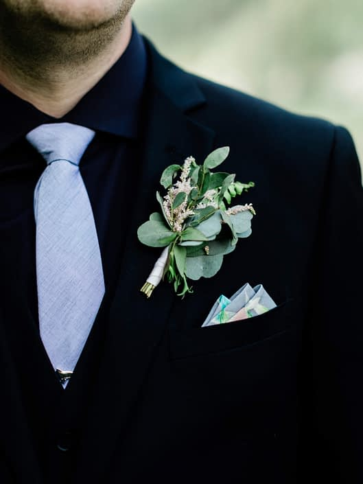 Groom's boutonniere made of pale pink astilbe, and eucalyptus greenery.