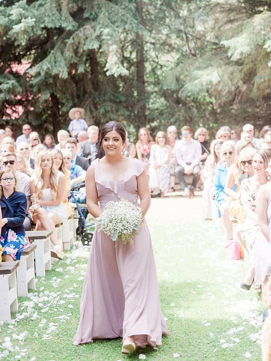 Bridesmaid wearing floor length dusty rose dress and holding a bouquet made of babies breath down a rose petal lined aisle.