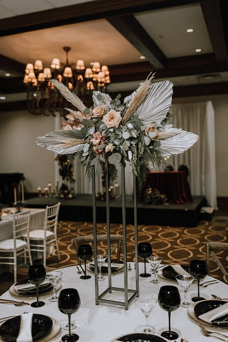 Cambridge Bridal Show 2020 - dramatic tall structural arrangement made of dyed metallic Anahaw palm leaves, pampas grass, blush roses and eucalyptus greenery.