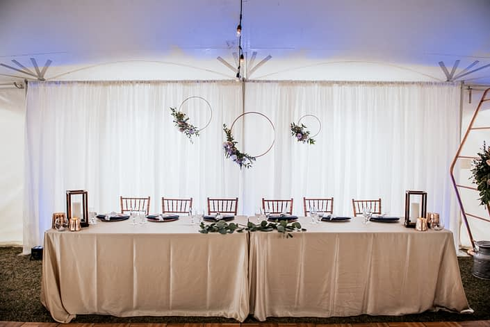 Erin and Nick's Mauve and Navy Winter Wedding Head Table decorated with copper hoops with floral accents