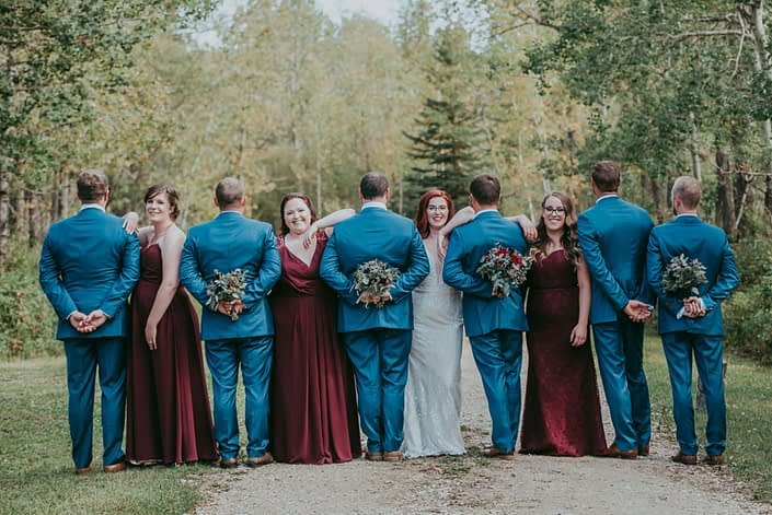 Hailey and Brandon's bridal party; bride and bridesmaids facing camera, groom and groomsmen holding bouquets with backs to camera