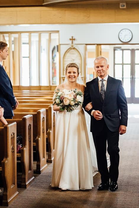 Bride and father walking down the aisle; bride holding natural hand-tied bouquet designed with quicksand roses, white o'hara garden roses, white ranunculus, light pink astilbe and a mixed variety of eucalyptus greenery.