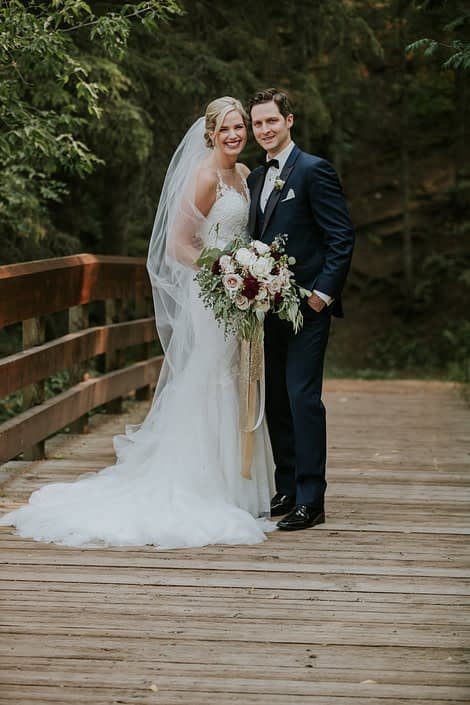 bride and groom on a bridge with wedding dress and veil and navy suit holding a bouquet designed with eucalyptus, burgundy dahlia and white and blush roses