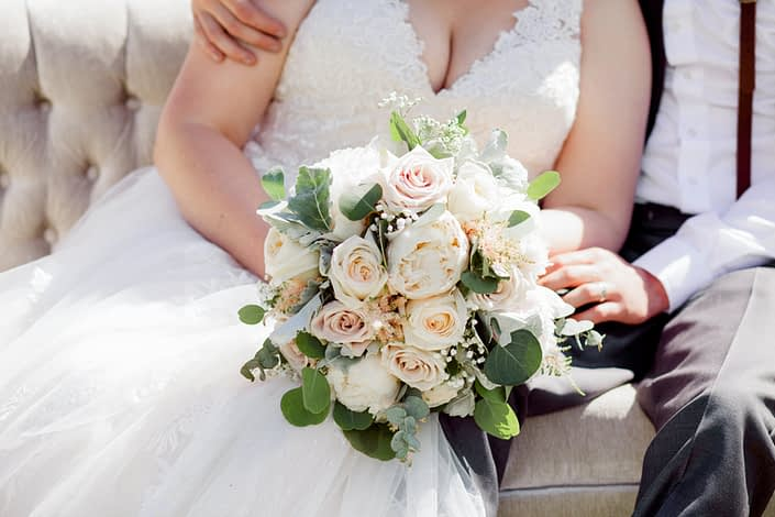 Bride, Kuera, wearing an ivory lace bridal gown and holding a cream and blush bouquet featuring white peonies, quicksand roses, white o'hara garden roses, pink astilbe, gypsophila, dusty miller and eucalyptus.