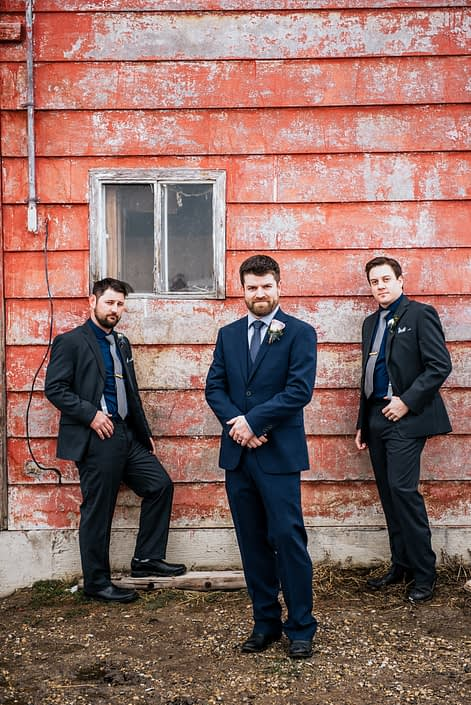 Nick and groomsmen wearing boutonnieres made with mauve, ivory and blye flowers