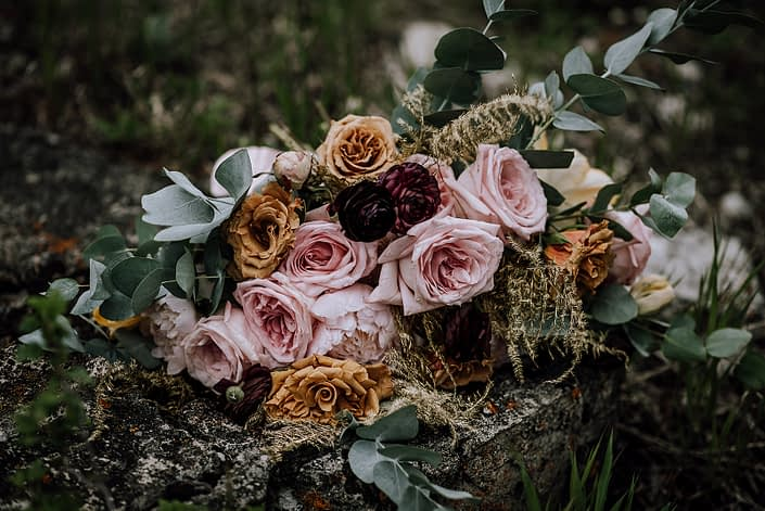 Close up photo of bride bouquet designed with pink oahara garden roses, toffee roses, gold plumosa, and eucalytpus