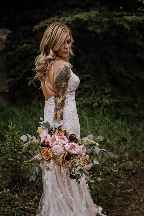 Tattoo sleeve bride in white lace wedding dress holding organic bridal bouquet of pink o'hara roses, toffee roses, cinerea eucalyptus and gold plumosa