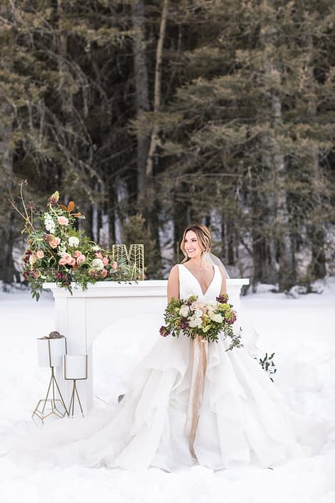 Bride in winter wedding styled shoot holding bouquet in front of mantle with floral arrangements and bridal bouquet in burgundy, blush and white