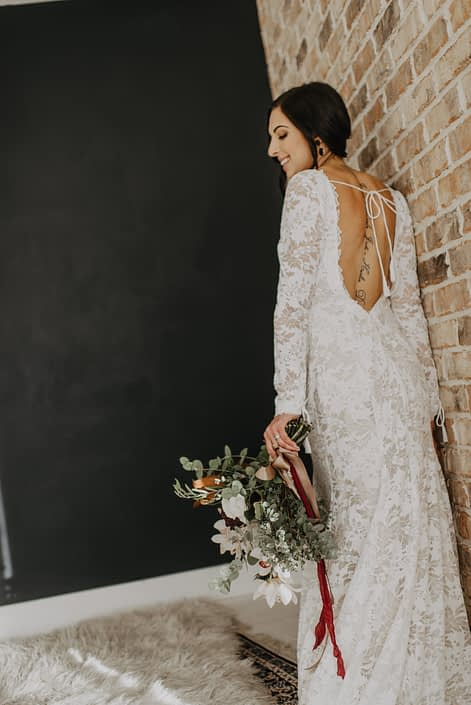 Neutrals Styled Shoot with Down the Aisle -Bride wearing lace gown holding a neutral coloured bouquet with ivory flowers and greenery tied with trailing ribbons.