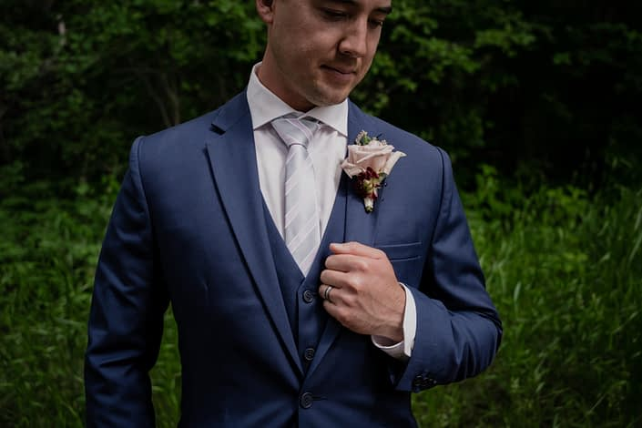 Groom boutonniere designed with a quicksand rose accented by a burgundy dahlia bud, astilbe and greenery